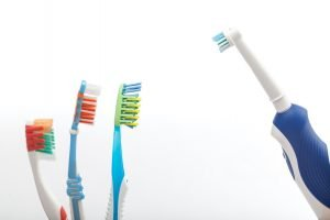 Three toothbrushes on white against the electric toothbrush